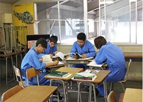 国家試験受験対策の授業にて訓練生が円になるように机を寄せ合って教科書を持って学んでいる様子