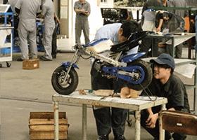 オープンキャンパスにて参加者がバイクのエンジンに触れている様子