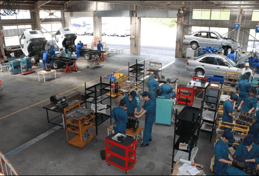 手前側の1年生はエンジン単体の分解・組立の訓練、奥側の2年生はトラックの車検整備の訓練を実施している様子