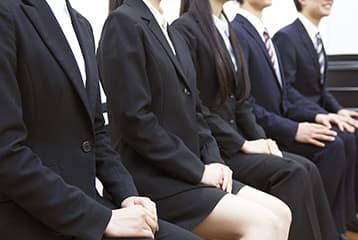スーツを着た学生が集団面接を受けている様子