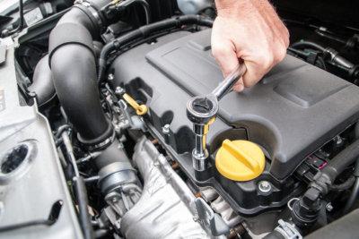 整備の一環である自動車のトランク内のネジを閉めている写真