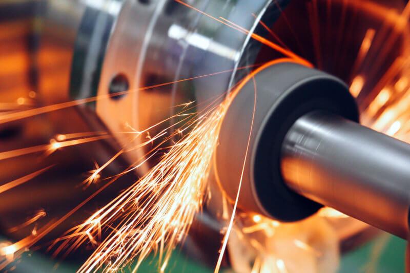 研削といしを使用し、火花を散らしながら回転させて加工材の研削作業を行っている写真